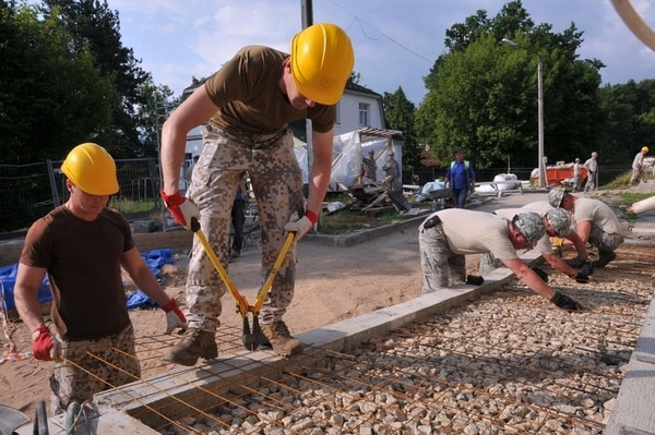 Airmen and Latvian soldiers work together on a cement ramp at the Naujene Orphanage in Latvia. (Senior Airman Allyson L Manners/Air Force)