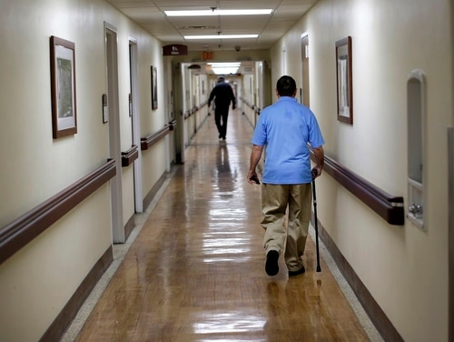 A patient walks down a hallway at the Fayetteville Veterans Affairs Medical Center in North Carolina in March 2015. Critics and supporters of plans to expand veterans access to private-sector medical appointments are gearing up for a new round of fights after the release of new draft community care rules this week. (Patrick Semansky/AP)