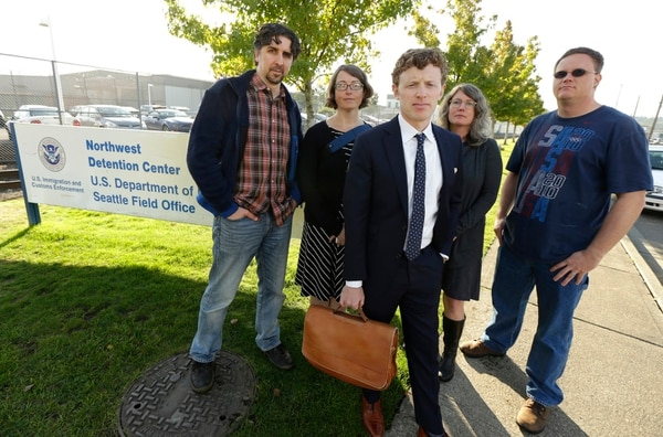 Tim Warden-Hertz, center, an attorney with the Northwest Immigration Rights Project who is representing Chong Kim, poses for a photo with friends and supporters of Kim, Wednesday, Oct. 4, 2017, outside the Tacoma Northwest Detention Center in Tacoma, Wash. An immigration judge Wednesday declined to release Kim from custody while Kim fights the government's efforts to deport him. (Ted S. Warren/AP)