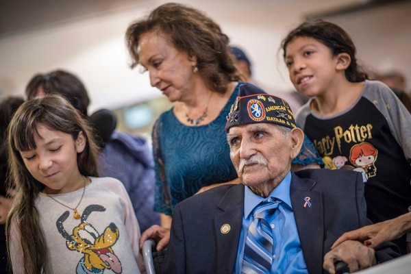 In a Sept. 23, 2017 photo, Bataan Death March survivor Joe Romero, bottom, is surrounded by his caretaker Nora Cruz, center back, and her granddaughters Mia Garcia, 10, left, and her sister Olivia Garcia ,12, right, during a ceremony in which Romero was presented with the Bronze Star as well as other medals as he also celebrated his 97th birthday. (Roberto E. Rosales/The Albuquerque Journal via AP)