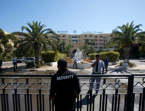 A security officer guards the entrance to the Imperial Marhaba hotel which was attacked on Friday in Sousse, Tunisia, Saturday, June 27, 2015. The morning after a lone gunman killed dozens of people at a beach resort in Tunisia, busloads of tourists are heading to the nearby Enfidha-Hammamet airport hoping to return to their home countries. (AP Photo/Darko Vojinovic)