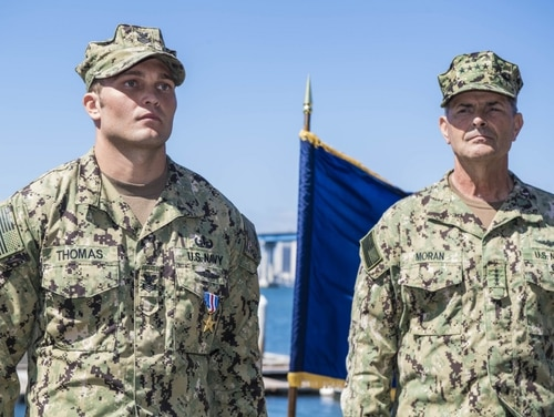 Explosive Ordnance Disposal Technician 1st Class Jeffrey Thomas stands at attention alongside Vice Chief of Naval Operations Adm. Bill Moran after being awarded the Silver Star (MC3 Christopher A. Veloicaza).