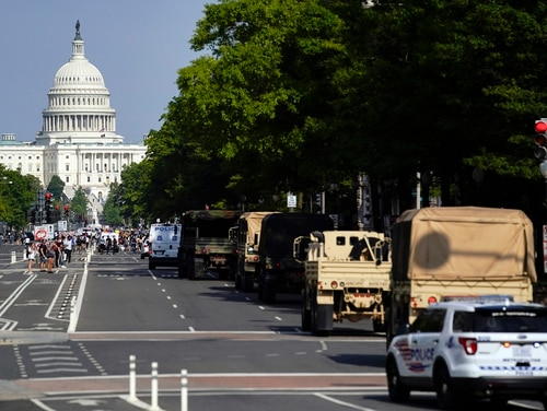 Demonstrators walk along Pennsylvania Avenue as a line of police and military vehicles drive as they protest the death of George Floyd, Wednesday, June 3, 2020, in Washington. Floyd died after being restrained by Minneapolis police officers. (Evan Vucci/AP)
