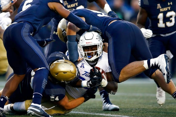 Navy defenders tackle Tulsa running back Corey Taylor II, center, as he rushes the ball on Saturday in Annapolis. (Patrick Semansky/AP)