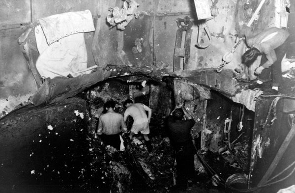 View of the damage to the aircraft carrier Yorktown. This crater on the third and fourth decks, amidships, was caused by a 250 kilogram bomb dropped during the Battle of Coral Sea on May 8, 1942. The large hole in the deck was made by the bomb's explosion. Many men were killed or badly injured in C-301-L, a crew's messing space that was the assembly area for the ship's engineering repair party. (U.S. Naval History and Heritage Command)