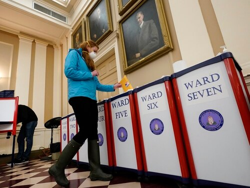 A voter drops her ballot into the box during early in-person voting at city hall in Somerville, Mass., on Oct. 29, 2020. (Elise Amendola/AP)