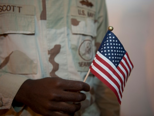 A Navy petty officer 3rd class holds a miniature American flag given to him by fellow sailors as he officially became an American citizen at Camp Lemonnier, Djibouti, on Jan. 25, 2012. (Staff Sgt. Andrew Caya/Air Force)