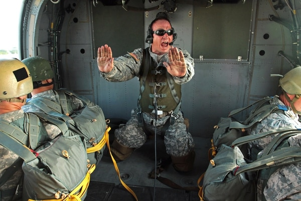 Sgt. 1st Class William Baker, a jumpmaster assigned to Special Operations Command South, yells instructions to paratroopers before they jump out of a MH-60 helicopter during a rotary-wing airborne operation April 16 at Homestead Air Reserve Base, Fla. (Sgt. 1st Class Alex Licea/Army)