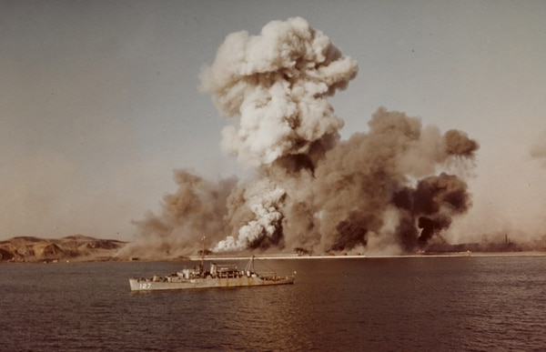 Smoke rises over Hungnam's port area, as remaining UN supplies are blown up on the final day of evacuation operations, 24 December 1950. The Navy's Crosley-class high speed transport Begor is in the foreground. (U.S. Naval History and Heritage Command)