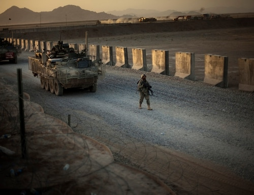 U.S. soldiers walk next to armored vehicles as they arrive at their base on the outskirts of Spin Boldak, about 100 kilometers (63 miles) southeast of Kandahar, Afghanistan, on June 13, 2021. (Emilio Morenatti/AP)