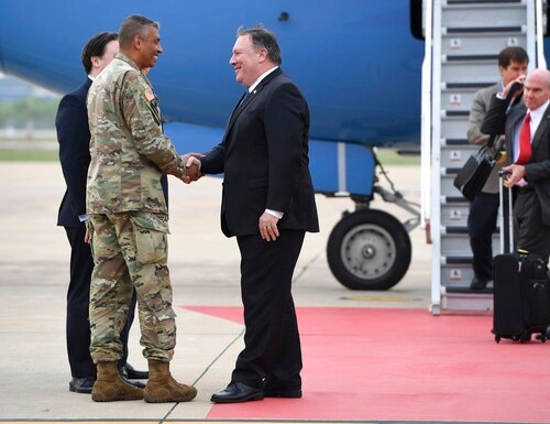 U.S. Secretary of State Mike Pompeo, center, shakes hands with Gen. Vincent K. Brooks, commander of United States Forces Korea, upon his arrival at Osan Air Base in Pyeongtaek Wednesday, June 13, 2018. South Korea's presidential office said Pompeo will meet President Moon Jae-in Thursday morning to discuss the meeting, which made history as the first between sitting leaders of the U.S. and North Korea. (Jung Yeon-je/Pool Photo via AP)