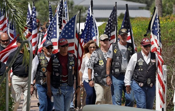 A motorcycle group carries American flags during an open funeral service for U.S. Army veteran Edward K. Pearson Tuesday, Oct. 1, 2019, at the Sarasota National Cemetary in Sarasota, Fla. (Chris O'Meara/AP)