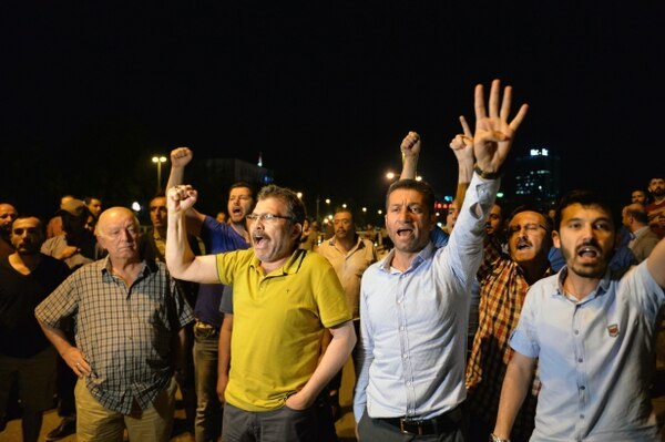 ANKARA, TURKEY - JULY 15: Supporters of Turkish President Recep Tayyip Erdogan chant slogans on the main streets on July 15, 2016 in Ankara, Turkey. Istanbul's bridges across the Bosphorus, the strait separating the European and Asian sides of the city, have been closed to traffic. Reports have suggested that a group within Turkey's military have attempted to overthrow the government. Security forces have been called in as Turkey's Prime Minister Binali Yildirim denounced an 'illegal action' by a military 'group', with bridges closed in Istanbul and aircraft flying low over the capital of Ankara (Photo by Kutluhan Cucel/Getty Images)