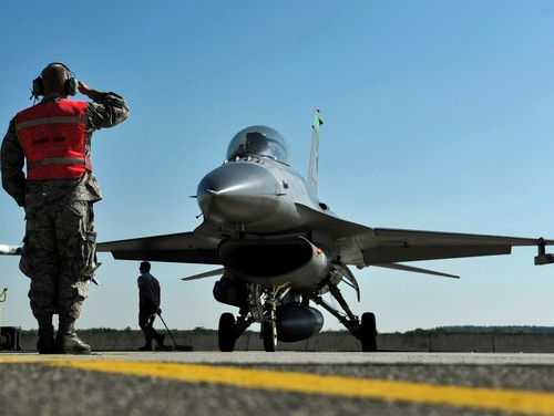 A weapons loader salutes an F-16 Fighting Falcon pilot as he prepares to take off for a training sortie at Kecskemet Air Base, Hungary. (Senior Master Sgt. Beth Holliker/Air National Guard)