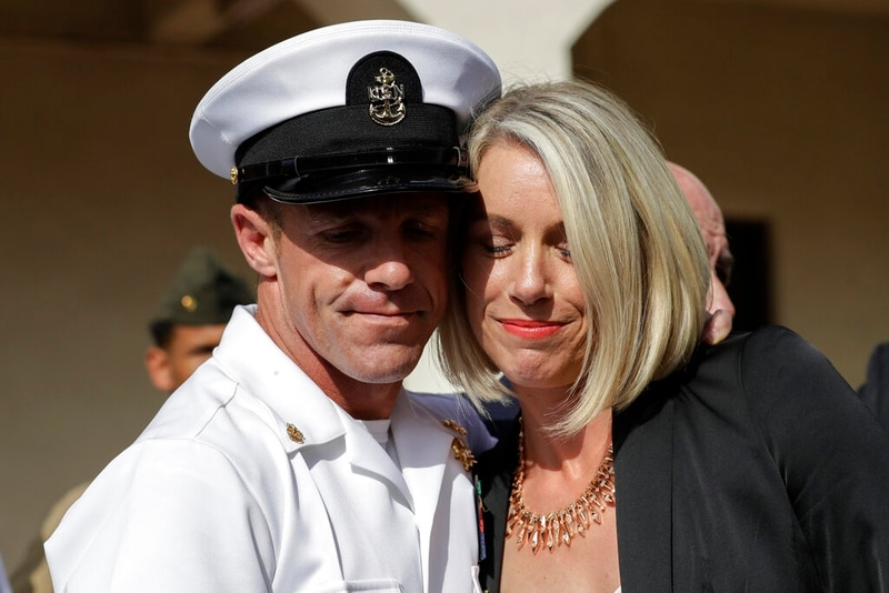 """Special Warfare Operator Chief Edward """"Eddie"""" Gallagher, left, and his wife Andrea hug after leaving the Naval Base San Diego courthouse on July 2 after he was cleared of all but one charge against him by a panel of his peers. (Gregory Bull/AP)"""