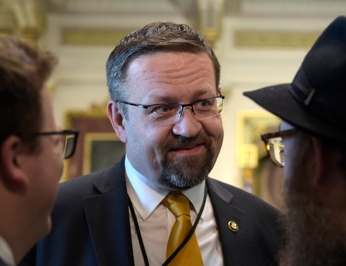 In this Tuesday, May 2, 2017 file photo, deputy assistant to President Trump, Sebastian Gorka, talks with people in the Treaty Room in the Eisenhower Executive Office Building on the White House complex in Washington during a ceremony commemorating Israeli Independence Day. White House national security aide Sebastian Gorka tells The Associated Press he has resigned from his position, Friday, Aug. 25, 2017. (AP Photo/Susan Walsh, File)