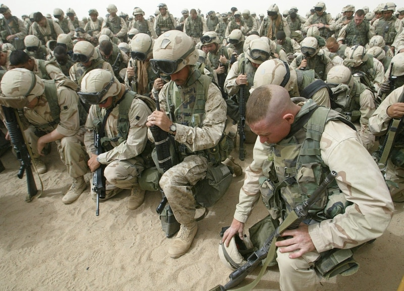 Marines kneel and pray as the 2nd Battalion, 8th Regiment prepares to leave Camp Shoup, north of Kuwait City, in a north-bound direction March 20, 2003. More than 150,000 allied troops gathered in positions near the Iraqi border to start their advance into southern Iraq. (Cris Bouroncle/AFP via Getty Images)