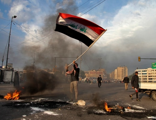 A protester waves the national flag while demonstrators set fire to close streets near Baghdad's Tahrir Square during a demonstration against the Iranian missile strikes. Iran struck back at the United States early Wednesday for killing a top Revolutionary Guard commander, firing a series of ballistic missiles at two military bases in Iraq that house American troops in a major escalation between the two longtime foes. (Khalid Mohammed/AP)