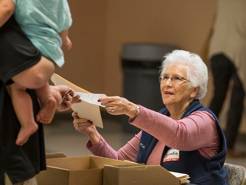 Poll worker Claudia Roberts, with the Leon County Supervisor of Elections office, hand a voter his ballot at the Lafayette Park precinct on Nov. 8, 2016, in Tallahassee, Florida. (Mark Wallheiser/Getty Images)