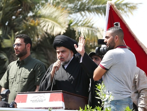 "Populist Shiite cleric Muqtada al-Sadr said any political party that would drag Iraq in a U.S.-Iran war ""would be the enemy of the Iraqi people."" al-Sadr, center, speaks to his followers demonstrating at Tahrir Square in Baghdad, Iraq, Friday, July 15, 2016. (Hadi Mizban/AP)"