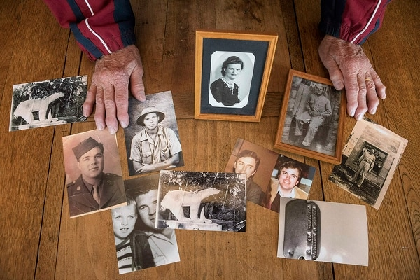 In this photo taken May 8, 2019, Andre Gantois shows family photos, including one of his mother Irene Gantois, top center, in Ludres, France. The retired French postal worker figured he'd likely go to his grave without ever knowing who his father was, unable to identify the U.S. serviceman who had fought his way across France after the D-Day landings, taken a bullet to the skull and been nursed back to health in a military hospital by Gantois' mother. (Jean-Francois Badias/AP)