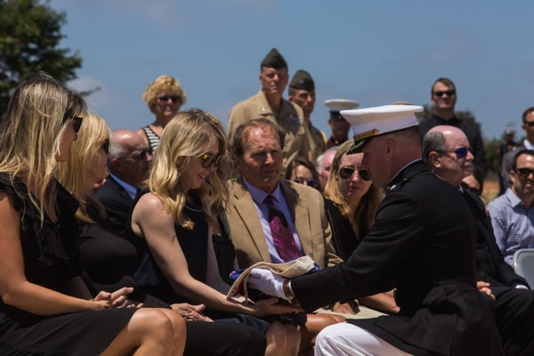 """Lt. Col. Wade Workman presents the flag of Maj. R. Sterling Norton, a fallen pilot with Marine Fighter Attack Squadron (VMFA) 232, to his wife during his funeral ceremony at the Miramar National Cemetery, San Diego, Aug. 12. Norton, a Santa Cruz, Calif., native, commissioned in the Marine Corps in 2005, graduated from the Navy Strike-Fighter Weapons School """"Top Gun"""" in 2013, and served as a weapons and tactics instructor and a strike-fighter tactics instructor during his career. His personal awards include the Meritorious Service Medal, the Navy and Marine Corps Commendation Medal, and the Navy and Marine Corps Achievement Medal with one gold star. (U.S. Marine Corps photo by Sgt. Lillian Stephens/Released)"""