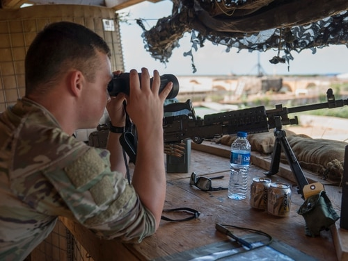 U.S. Army Private Dylan Yarbro, infantryman, assigned to Task Force Guardian, 41st Infantry Brigade Combat Team (IBCT), 1-186th Infantry Battalion, Oregon National Guard, uses binoculars to scan the horizon while on security watch in Somalia, on December 3, 2019. (Tech. Sgt. Nick Kibbey/ Air Force)