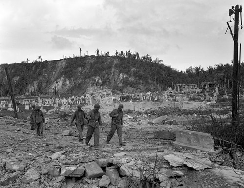 In this Aug. 9, 1944, file photo, U.S. soldiers walk by a bombed out cemetery in Agana, Guam. (Joe Rosenthal/AP)