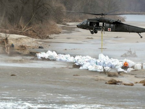 A crew with the Nebraska Army National Guard's 2nd Battalion, 104th Aviation Regiment, uses a UH-60 Black Hawk helicopter to lower 1,500-pound sandbags into place to stem flooding from a breached levee along the Loup River in Nebraska. (Staff Sgt. Natasha Hilsgen/Army)