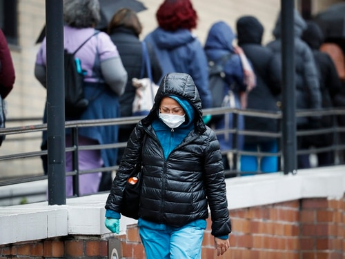 A medical worker wearing a single protective glove and a face mask walks past a line of workers and visitors waiting to be tested for COVID-19 at the main entrance to a Department of Veterans Affairs Medical Center on March 23, 2020, in New York. (John Minchillo/AP)