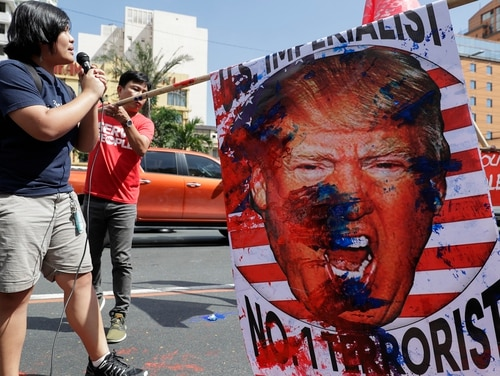 A protester on Monday in Manlia totes an image of U.S. President Donald Trump during a rally opposing the recent attack that killed Iranian Gen. Qassem Soleimani. Philippine President Rodrigo Duterte has ordered the military to prepare to deploy its aircraft and ships