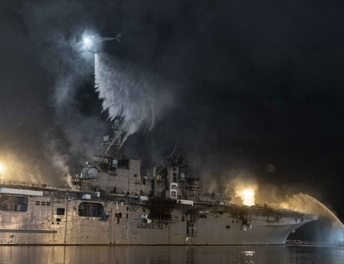 Helicopters drop buckets of water onto the exterior of the amphibious assault ship Bonhomme Richard Tuesday. (Navy)