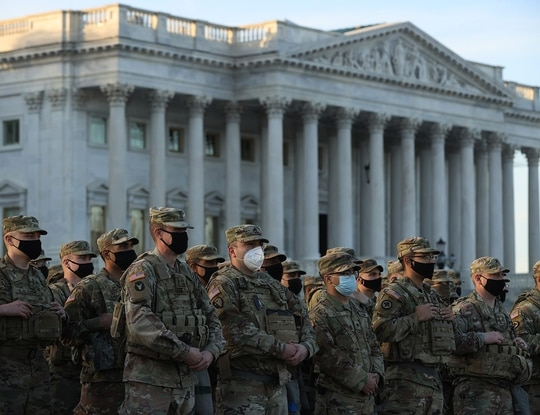 National Guard troops pose for photographers on the East Front of the U.S. Capitol the day after the House of Representatives voted to impeach President Donald Trump for the second time Jan. 14, 2021, in Washington. (Chip Somodevilla/Getty Images)