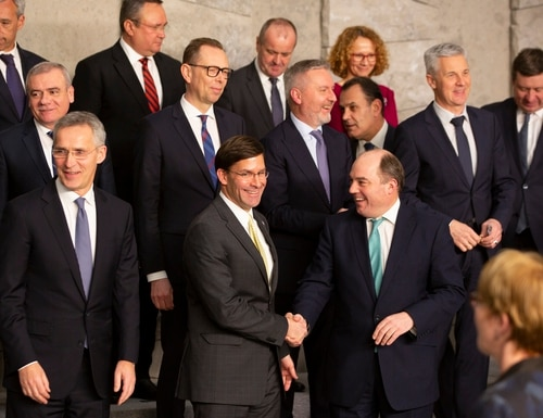U.S. Secretary for Defense Mark Esper, front center, shakes hands with British Defense Minister Ben Wallace during a group photo of NATO defense ministers at NATO headquarters in Brussels, Wednesday, Feb. 12, 2020. (Virginia Mayo/AP)