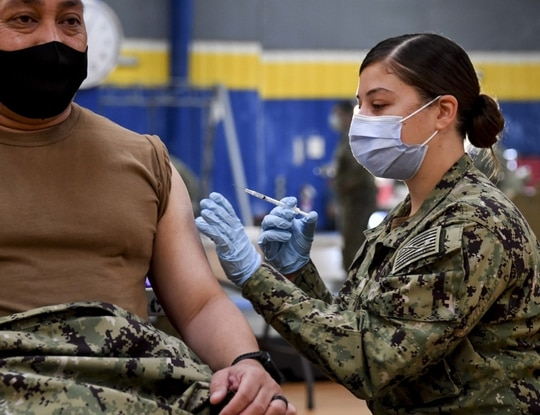Hospital Corpsman 2nd Class Angelina Mangram, assigned to Fleet Surgical Team 3, administers the COVID-19 vaccine at the Naval Base San Diego fitness center on Jan. 6, 2021. (MC1 Julio Rivera/Navy)