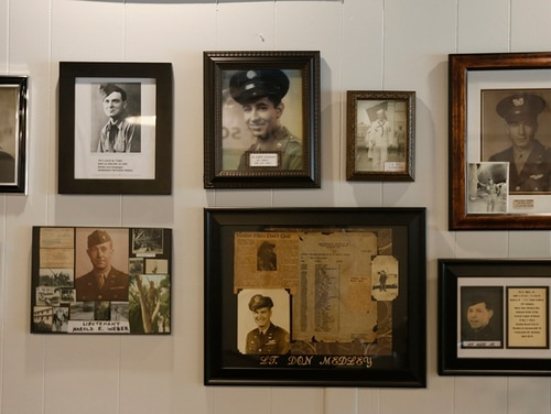 In this May 6, 2019, photo, a group of photos are on display at a tribute center for the Bedford Boys in Bedford, Va. The 75th anniversary of the D-Day invasion of Normandy has a solemn significance for Bedford, who lost 20 local men. (Steve Helber/AP)