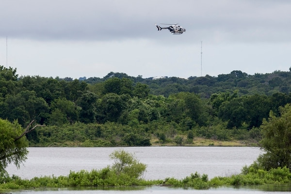 A Texas DPS helicopter flies over Lake Belton near the scene of an accident at Fort Hood at Owl Creek Park near Gatesville, Texas, on Thursday, June 2, 2016. Fort Hood says several soldiers are dead and six are missing after an Army troop truck was washed from a low-water crossing and overturned in a rain-swollen creek at Fort Hood in Central Texas. A statement from the Texas Army post says the accident happened about 11:30 a.m. Thursday in an area near Cold Springs and Owl Creek. (Michael Miller/The Temple Daily Telegram via AP) MANDATORY CREDIT