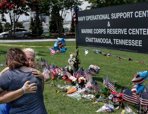 Sophia Ensley, right, and Barbie Branum embrace in front of a makeshift memorial at the Navy Operational Support Center and Marine Corps Reserve Center, Saturday, July 18, 2015, for the victims of the July 16 shootings in Chattanooga, Tenn. The U.S. Navy says a sailor who was shot in the attack on a military facility in Chattanooga has died, raising the death toll to five people. (Doug Strickland/Chattanooga Times Free Press via AP) THE DAILY CITIZEN OUT; NOOGA.COM OUT; CLEVELAND DAILY BANNER OUT; LOCAL INTERNET OUT; MANDATORY CREDIT