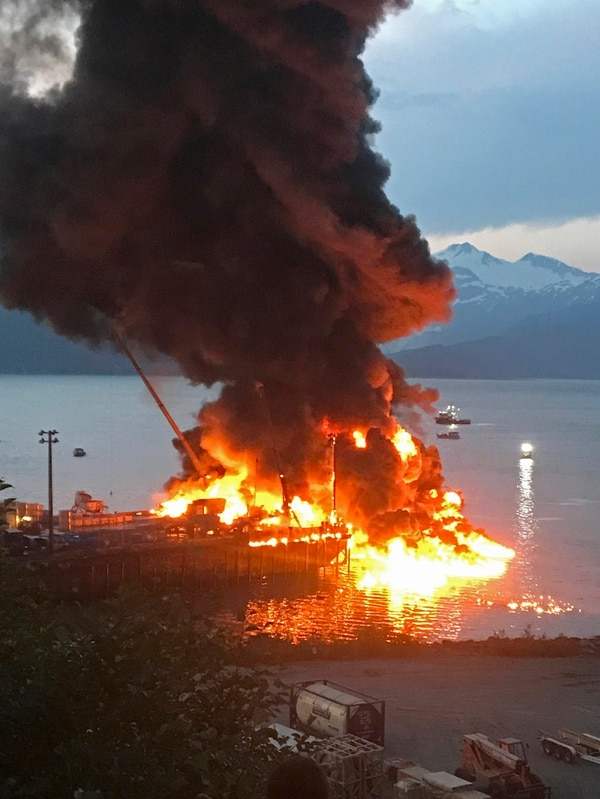 An explosion rocked a fishing boat tied up at a dock in Whittier, Alaska and spread fire to a nearby fishing boat that then sank, leaving one person aboard missing, the U.S. Coast Guard said Monday. (Brian Hicks/Girdwood Fire Department via AP)