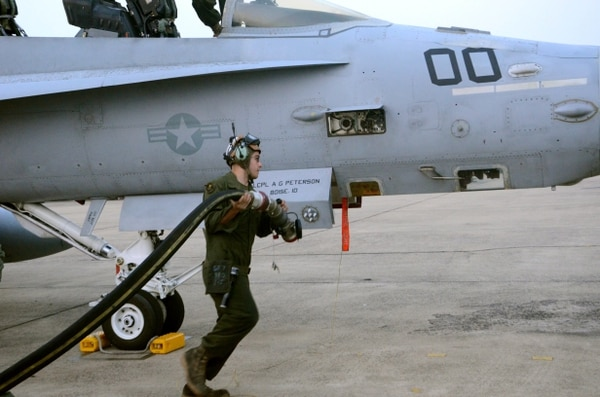 U.S. Marine Lance Cpl. Brian Zollars with the 242nd Fixed Wing Marine Fighter Attack (all weather) moves quickly to attach a fuel hose to an F-18 Hornet Feb. 15, 2016, during an early morning fuel up at Korat Royal Thai Air Force Base, Thailand. The 242nd is in Thailand in support of international training mission Cobra Gold 2016.