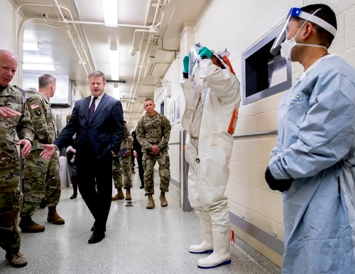Biological Science Specialists Reginald Clyburn, second from right, and Mark Ditching, right, wear biosafety level 3 and 4 protective clothing for handling viral diseases as Col. Darrin Cox, left, takes the Secretary of the Army Ryan McCarthy, third from left, and Gen. James McConville, Chief of Staff of the Army, second from left, on a tour of U.S. Army Medical Research and Development Command at Fort Detrick in Frederick, Md., on March 19, 2020. (Andrew Harnik/AP)