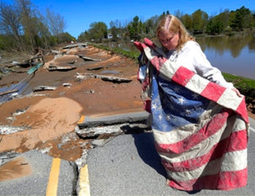 In this Thursday, May 21, 2020 photo, Kim Burgess, the mother of a Marine killed in Iraq, holds a muddy American flag after a dam failure destroyed a war memorial last week in Stanford, Mich. Burgess is pledging to rebuild the memorial. (Kirthmon F. Dozier/Detroit Free Press via AP)
