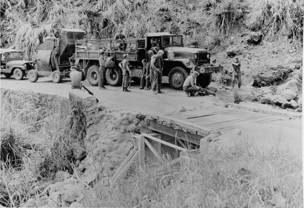 Seabees in Naval Mobile Construction Battalion 1 take a break on Aug. 2, 1967, while finishing work on a bridge near Da Nang, South Vietnam, which they are strengthening with a retaining wall and span bracing. (National Archives)