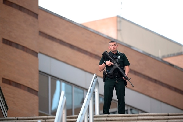 A police officer stands guard outside the Orlando Regional Medical Center hospital after a fatal shooting at a nearby Pulse Orlando nightclub in Orlando, Fla., Sunday, June 12, 2016. (AP Photo/Phelan M. Ebenhack)