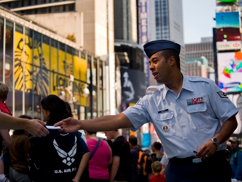 Staff Sgt. Bryan Rivera, an Air Force recruiter, hands business cards to potential recruits in Times Square during Air Force Week-New York Aug. 26. (Tech. Sgt. Bennie J. Davis III/Air Force)