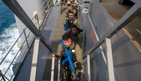 Sailors climb a ladder well during visit, board, search and seizure training on board the amphibious dock landing ship Fort McHenry on Jan. 20. The Navy began debating possible links between issued safety boots and ladder well injuries in 2016, according to documents leaked to Navy Times. (Mass Communication Specialist 3rd Class Chris Roys/Navy).