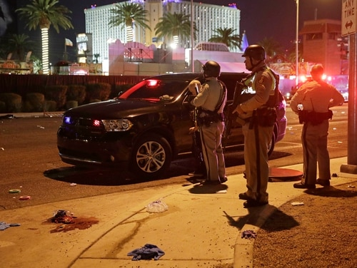 Police stand at the scene of a shooting along the Las Vegas Strip, Monday, Oct. 2, 2017, in Las Vegas. Multiple victims were being transported to hospitals after a shooting late Sunday at a music festival on the Las Vegas Strip. (AP Photo/John Locher)