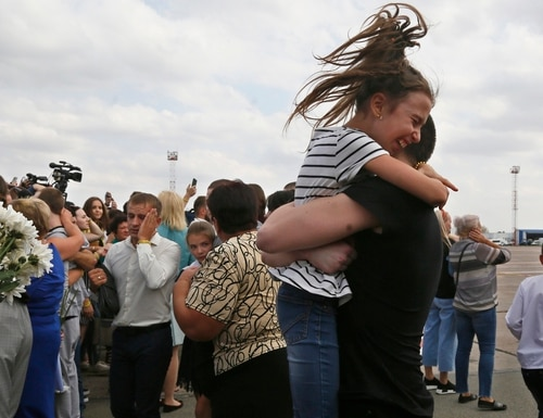 Relatives of Ukrainian prisoners freed by Russia greet them upon their arrival at Boryspil airport, outside Kyiv, on Saturday. (Efrem Lukatsky/AP)