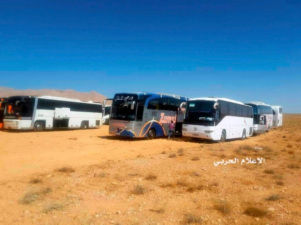 This photo provided Aug 28, 2017, by the government-controlled Syrian Central Military Media, shows buses gathering before a planned evacuation of Islamic State group militants in the mountainous region of Qalamoun, Syria. (Syrian Central Military Media via AP)