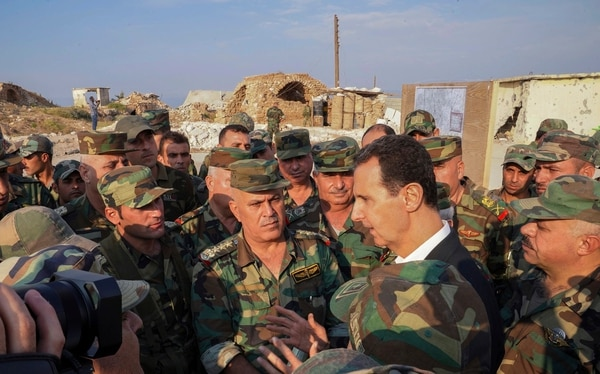 Syrian President Bashar Assad, center right, speaks with Syrian troops during his visit to the strategic town of Habeet, in the northwestern province of Idlib, Syria, Tuesday, Oct. 22, 2019. (Facebook page of the Syrian Presidency via AP)